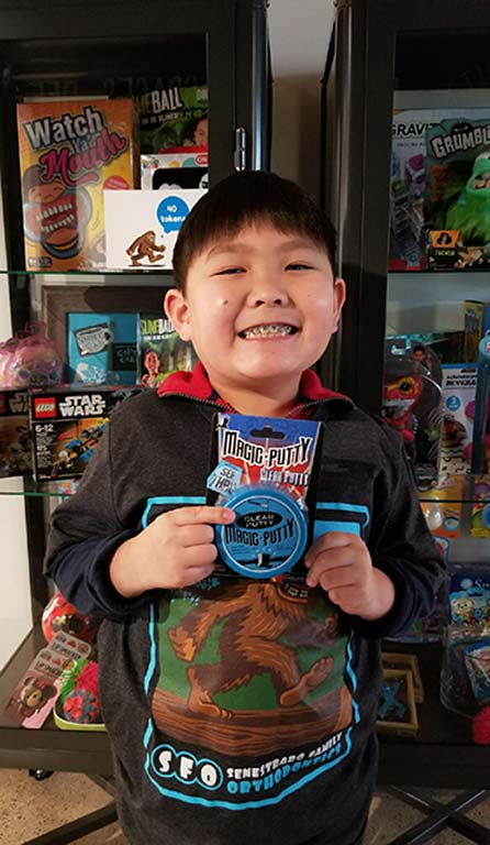 A boy holding token in the store at Senestraro Family Orthodontics