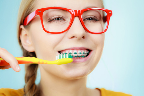 Young girl cleaning her braces
